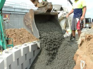 Excavator dumping no fines concrete into place at a construction project